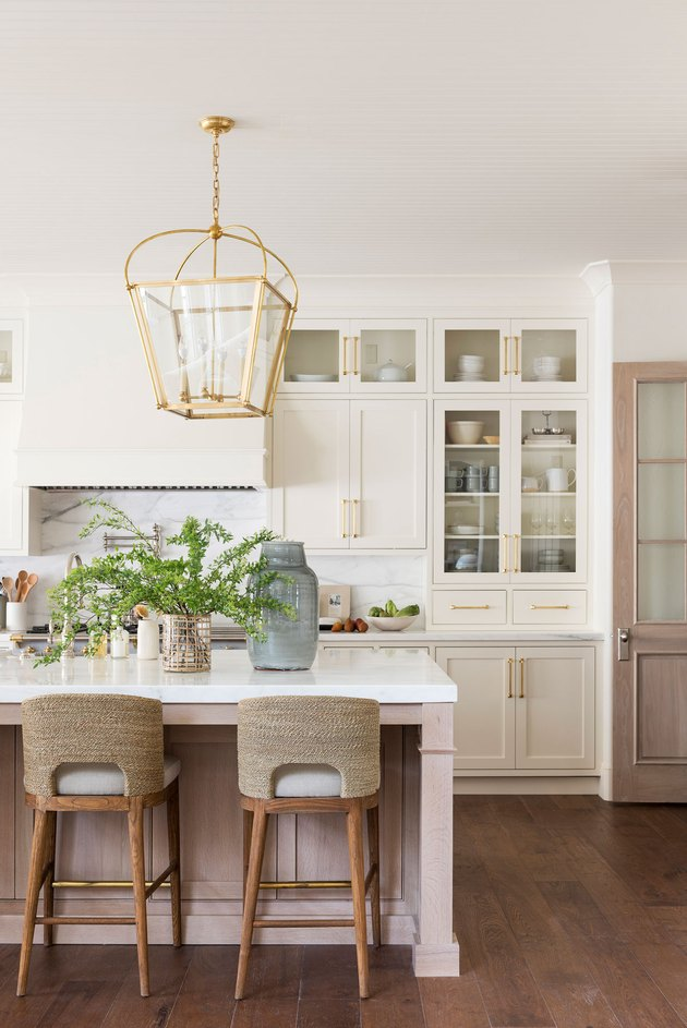 white kitchen space with two stools and hanging light fixture