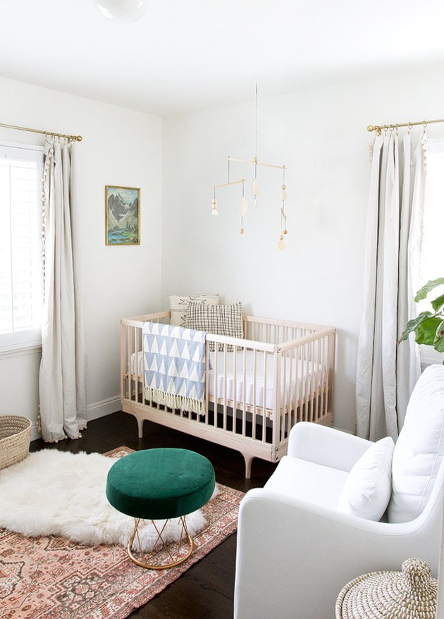 modern nursery idea with white walls and layered rugs with wooden crib
