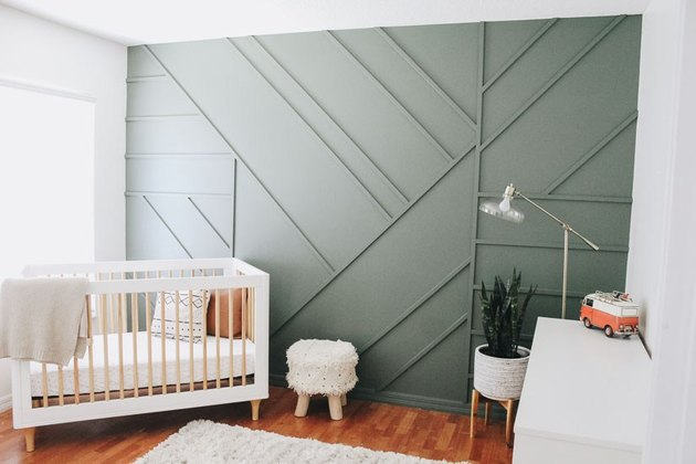 modern nursery idea with green wall panel and white crib