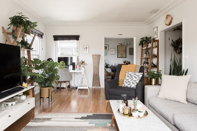 living room with greenery, white walls and hardwood floors