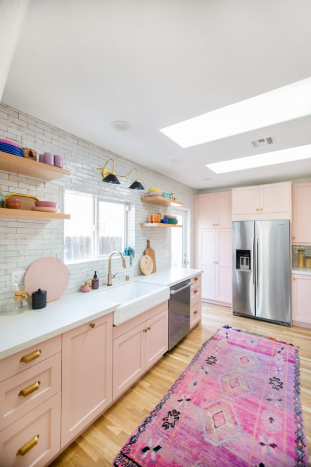 pink kitchen color idea with rosy cabinets and a moroccan rug with subway tile backsplash and open shelving