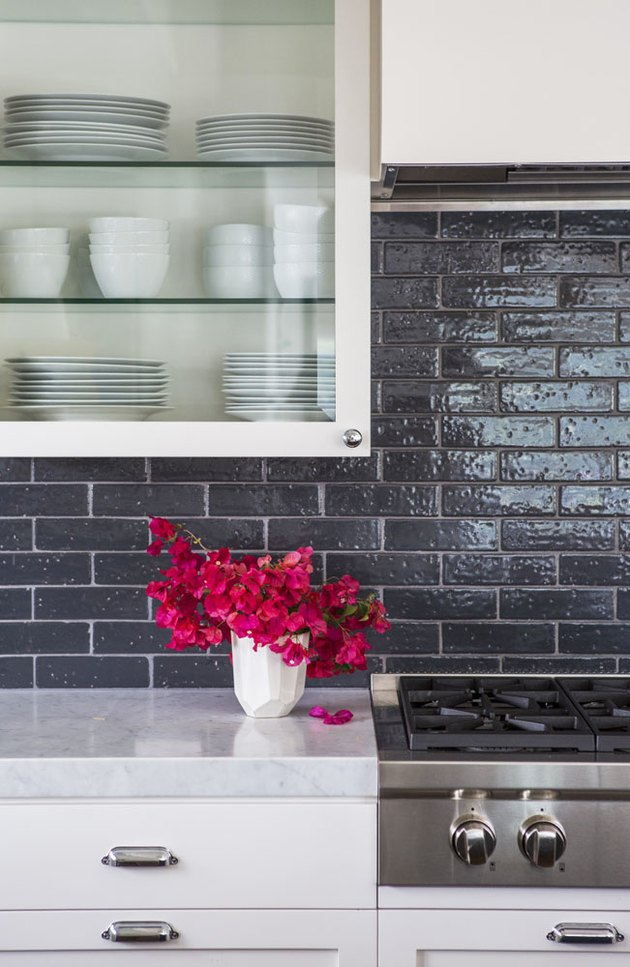 white glass kitchen cabinet with black backsplash and vase with red flowers