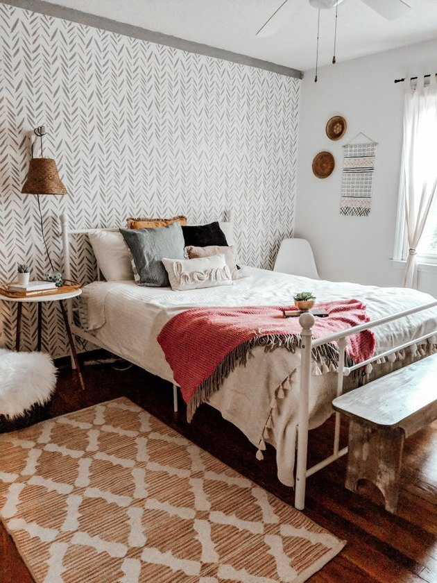 bohemian bedroom idea with red, white, and green decor and stenciled accent wall