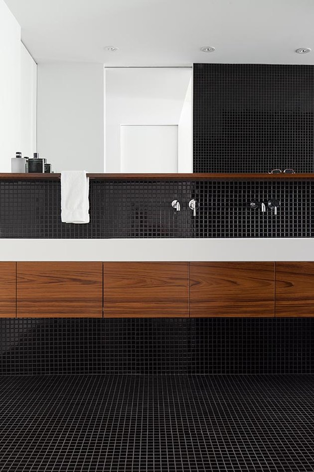 black bathroom with black mosaic floor and wall tile