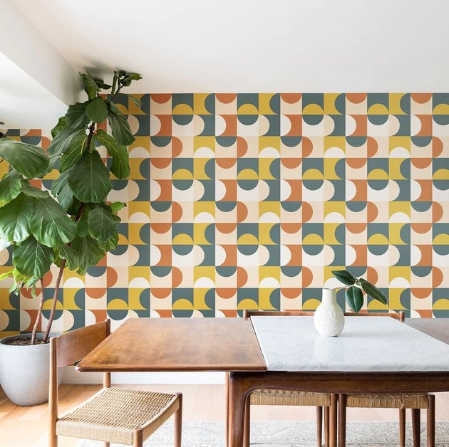 Blue, orange, white, and yellow midcentury modern wallpaper in dining room