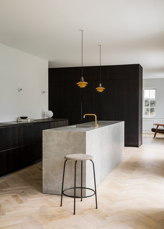large open minimalist kitchen with dark wood cabinets and herringbone wood flooring