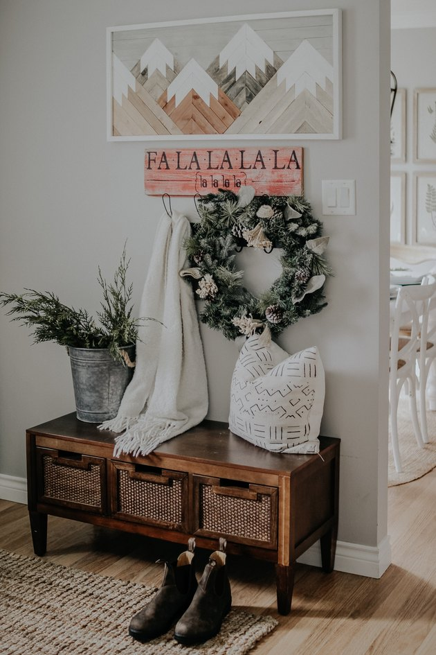 farmhouse Christmas decorating idea for entryway with Christmas wall art and winter greens