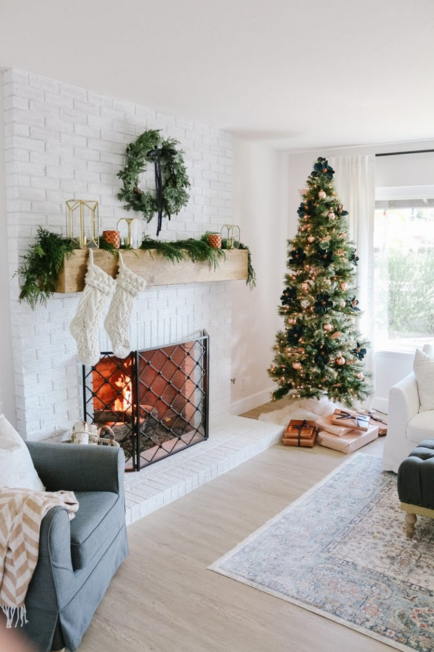 Neutral  farmhouse Christmas decorating idea in the living room with mantle and Christmas tree