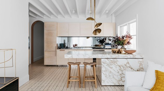 large open kitchen with modern brass chandelier above marble island