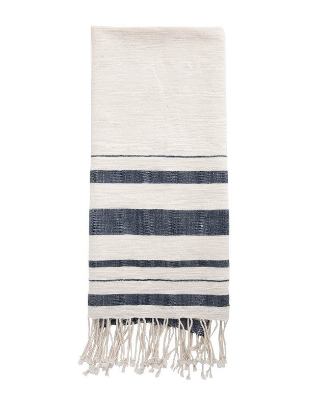 Mostly white handtowel with varied denim blue stripes near the bottom and white fringe