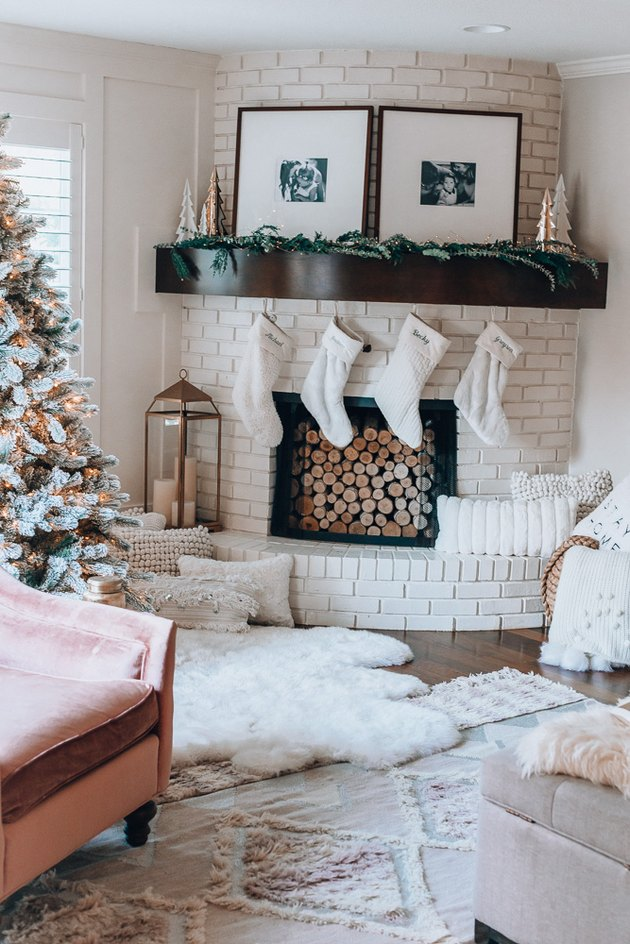 White  farmhouse Christmas decorating idea for living room with stockings, textiles, and Christmas tree