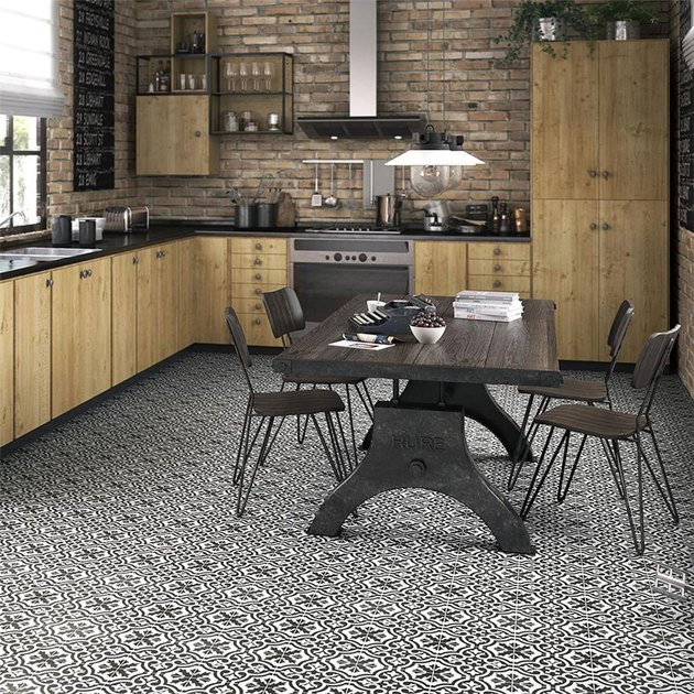 industrial kitchen with black and white ceramic floor tile and brick walls