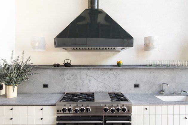 Gray soapstone countertops with white cabinets and black hood