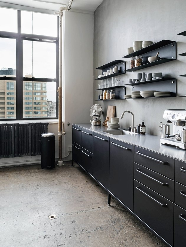 Black cabinetry and shiny silver countertops