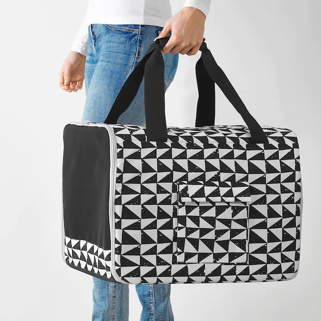 person holding black and white patterned cat bag