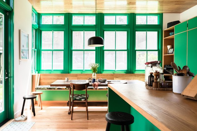 A built-in kitchen table surrounded by tall windows with green trim