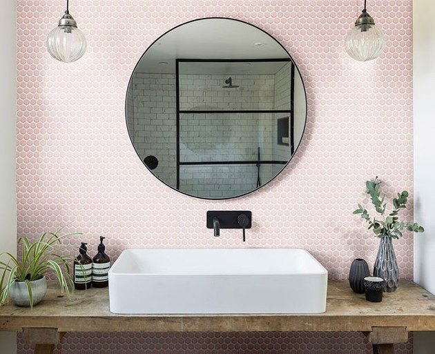 blush pink penny tile bathroom backsplash idea behind round mirror