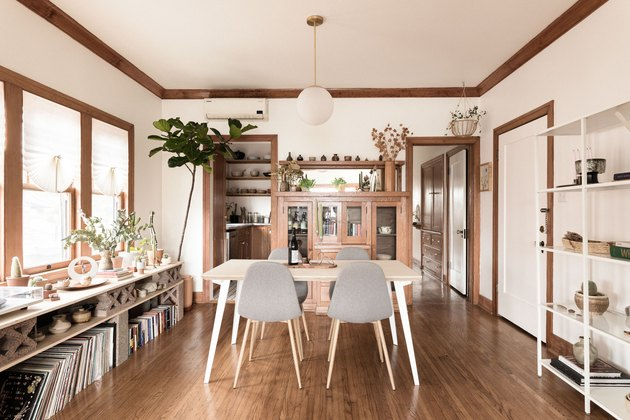 Hardwood dining room with wood trim, white walls and midcentury table