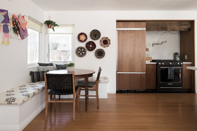 Dining room and kitchen with benches, a round wood table and hardwood floor