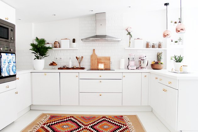 white kitchen with brass hardware and copper pendant lights