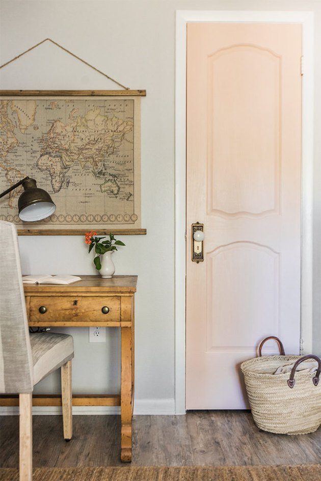 vintage farmhouse decorating idea with pink bedroom door and vintage map