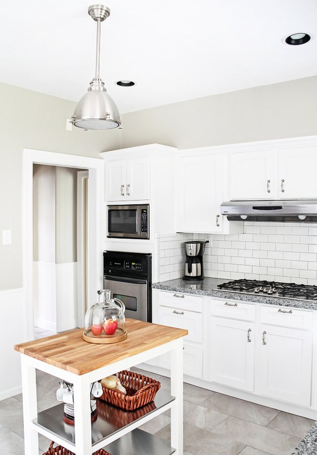 white kitchen with white subway tile and moveable island