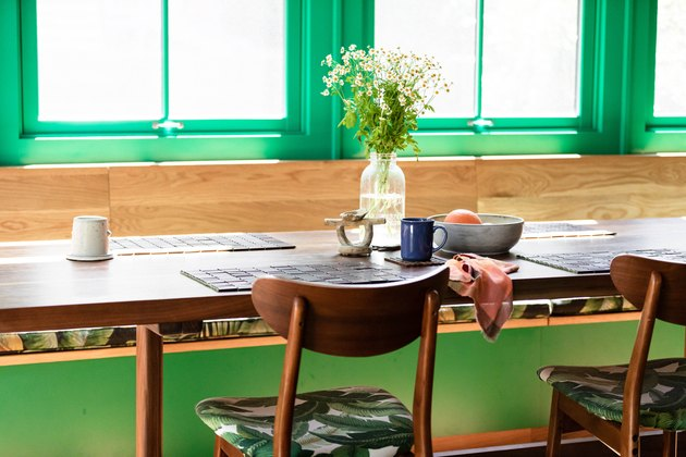 green window trim behind a wood breakfast table with wood chairs and flower on the table