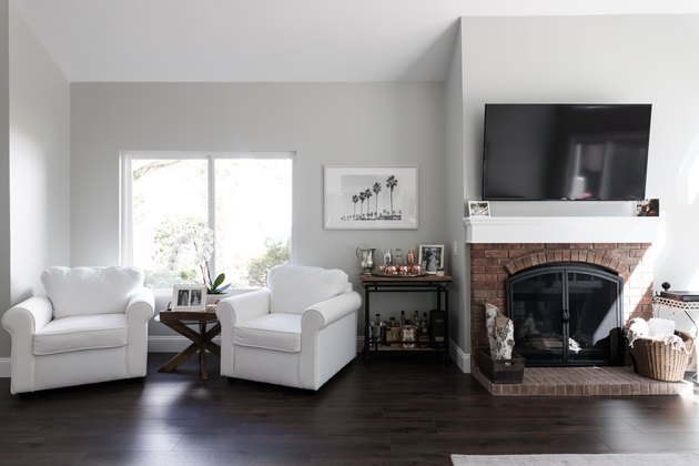 living room with light grey walls, light furniture, and dark floors