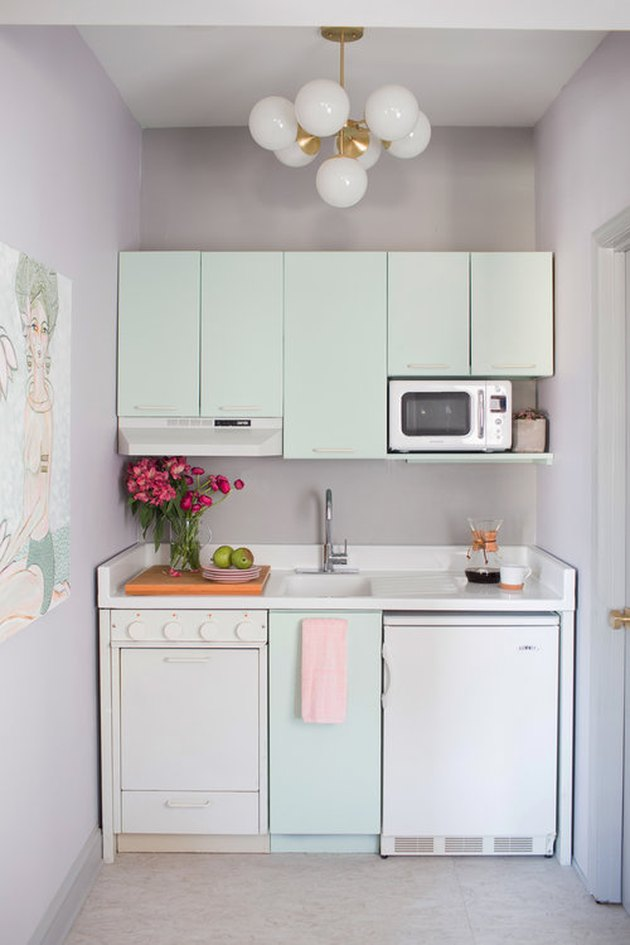 small retro mint green kitchen with white appliances and countertop