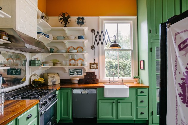 orange kitchen color idea with green cabinets and open shelving