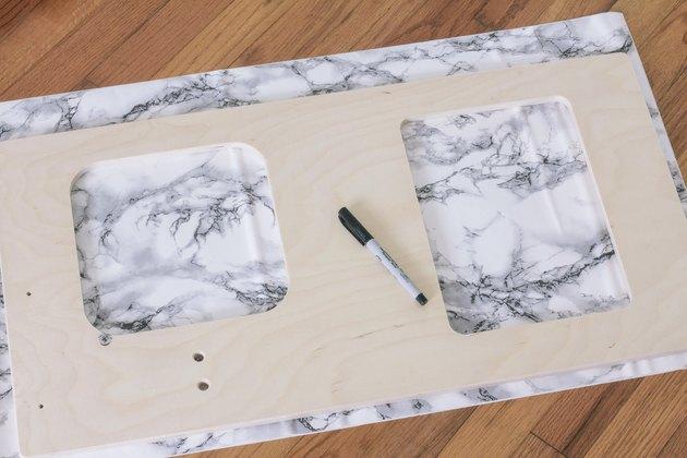 Traçage des formes de l'évier et du poêle sur du papier contact