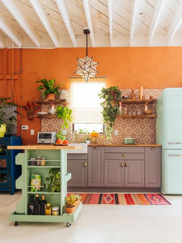 orange kitchen color idea with purple cabinetry and blue fridge