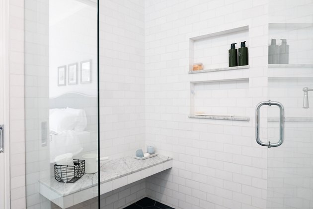 subway tile shower with marble bench