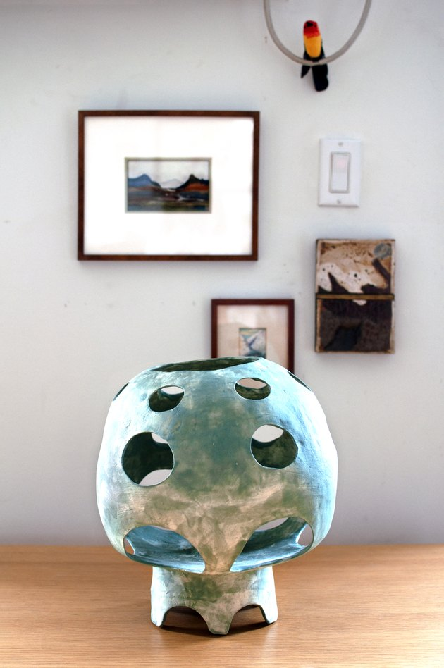 sculpture on a table with framed artwork in the background