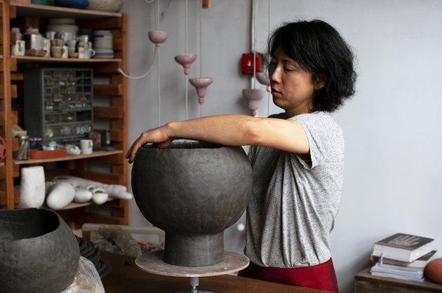 figure working on a ceramic piece in studio space