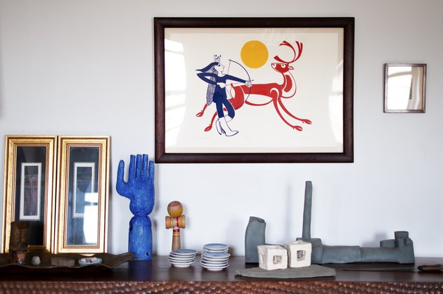 decorative objects on cabinet and framed artwork on the wall