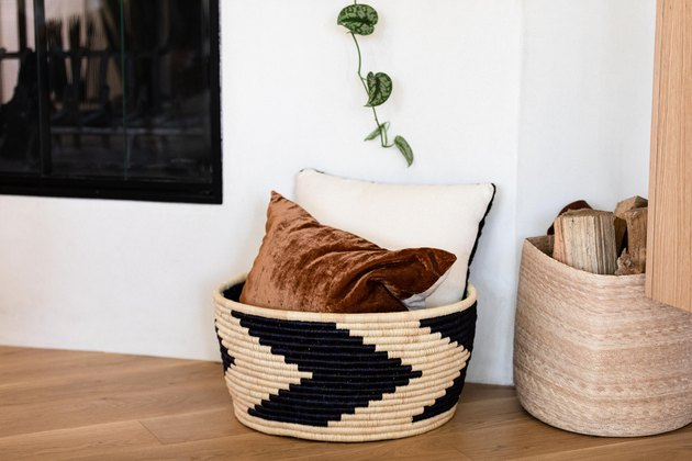 basket with two throw pillows next to a fireplace on a hardwood floor