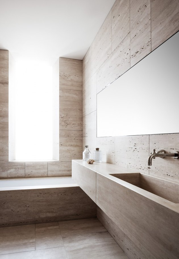 Floor to ceiling travertine bathroom with minimalist accents