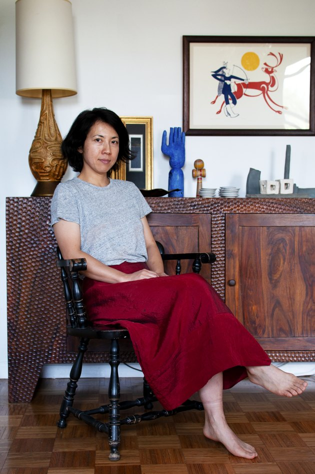 figure sitting on black chair near wooden cabinet