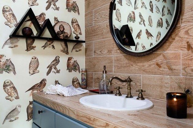 wood vanity top, white undermount sink with gold faucet, black triangular shelf, round mirror with black trim, bird wallpaper