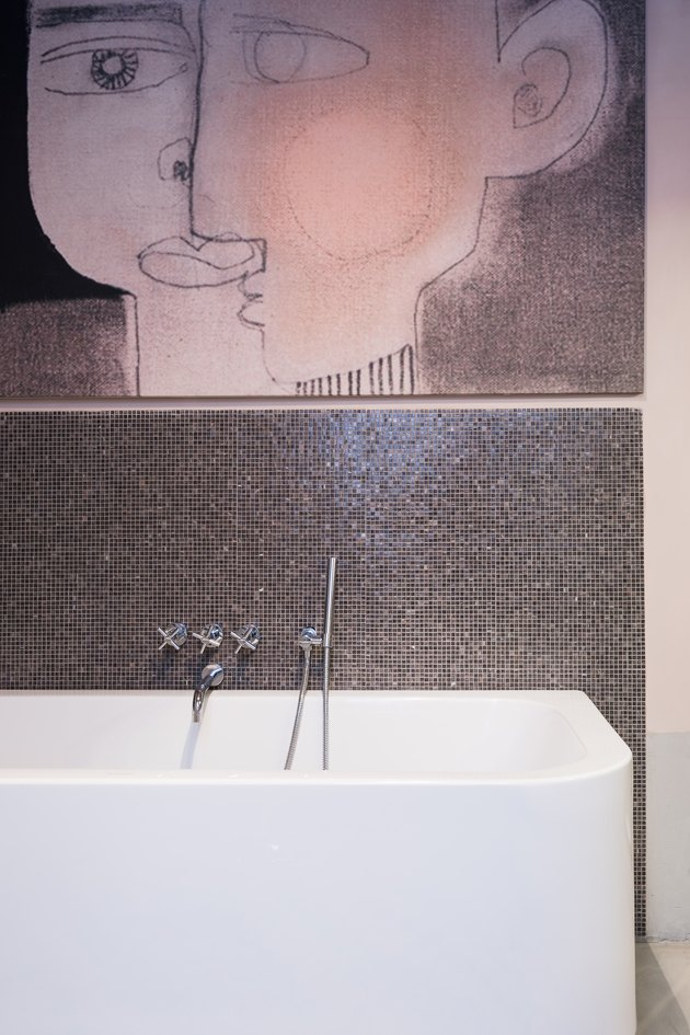 mosaic tile bathroom backsplash idea at bathtub with oversize artwork above