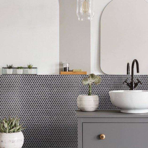 bathroom backsplash idea with gray penny tile behind vessel sink