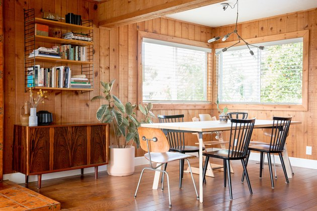 Midcentury modern dining room with wood walls and table with mismatched chairs