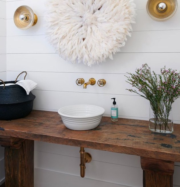 Shiplap and brass fixtures lend a farmhouse vibe to this bath.