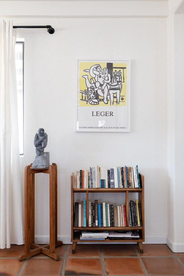 bookshelf, statue, and framed poster
