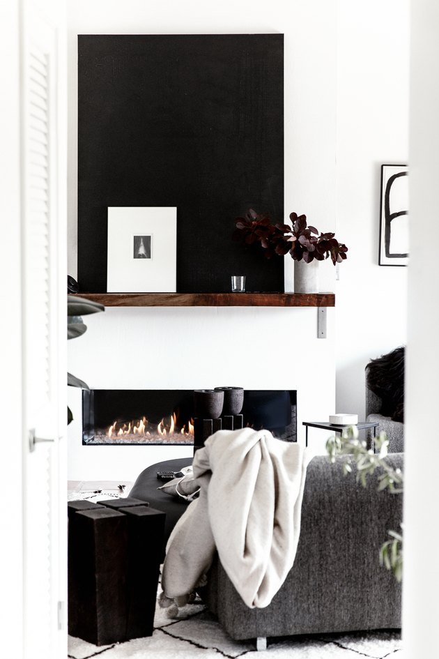 Modern black and white living  room with fireplace and wood mantel