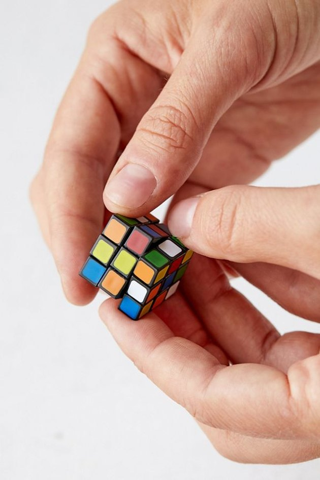 person playing mini rubik cube