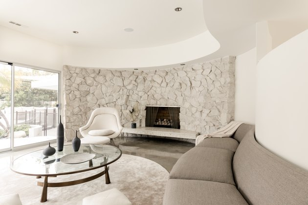 Curved stone fireplace surround in living room with curved furniture