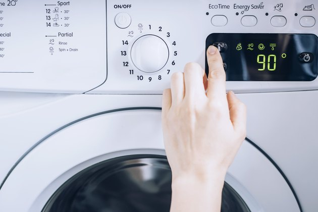 person using white washing machine with temperature controls