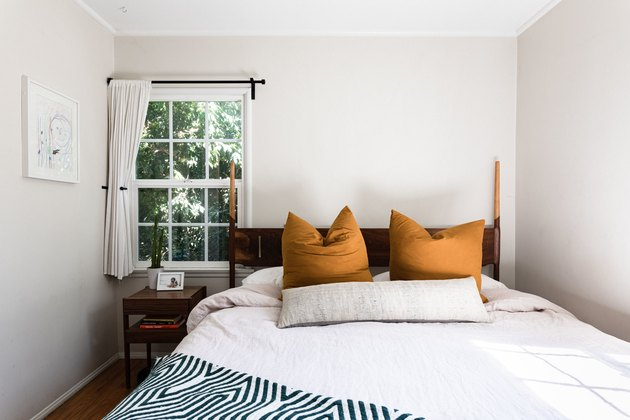 bedroom with white cover and two mustard pillows